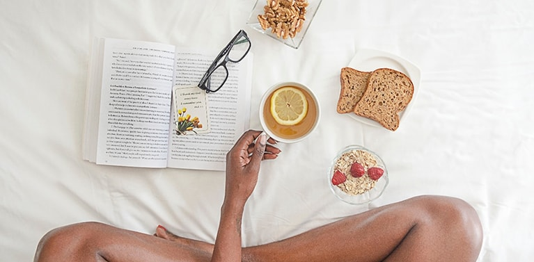A girl sat on a bed with a book and healthy food