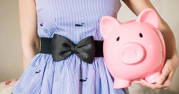A lady holding a pink piggy bank