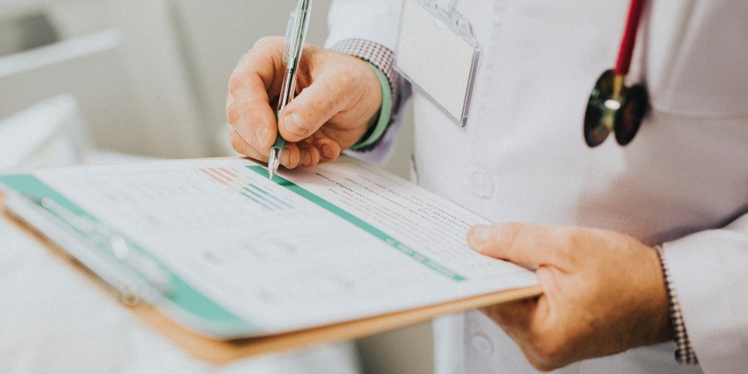 Doctor looking at patient notes on clipboard